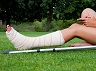 Girl with leg in plaster using her smartphone